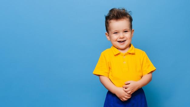 Симпатичные маленькие гримасы стоит на синем фоне. забавный ребенок