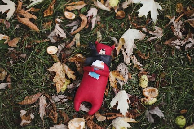 秋の庭でかわいい小さな手作りのテディベアのおもちゃ