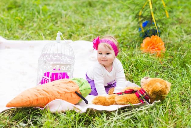 緑の草の牧草地、春または夏のシーズンに大きな茶色のテディベアとかわいい小さな幸せな赤ちゃん女の子。