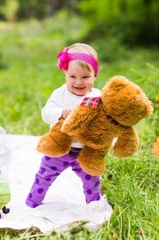 Милая маленькая счастливая девочка с большим коричневым плюшевым мишкой на лугу зеленой травы, весной или летом.