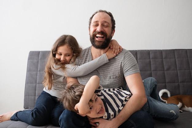 Милая маленькая счастливая кавказская девочка и мальчик обнимают отца. лучшие друзья. сын и дочь. братья и сестры. счастливая семья. веселиться.