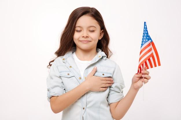 Милая маленькая счастливая девушка держит американский флаг и трогает ее грудь, выражая счастье и стоя с закрытыми глазами, изолированными на белой стене