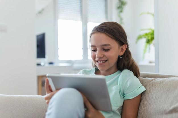 自宅のリビングルームでデジタルタブレットパッドを使用してソファに座ってかわいい幸せな女の子の笑顔。家族の活動の概念。