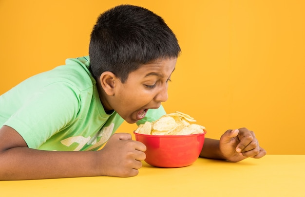 Cute little indian or asian boy eating chips or potato wafers in big red bowl, over yellow background