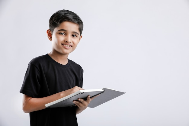 Cute little indian / asian boy reading book isolated