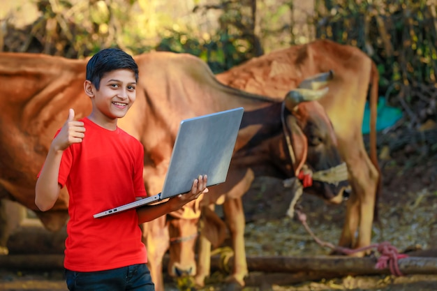 ラップトップコンピューターで勉強またはゲームをプレイしているかわいいインド/アジアの少年