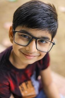 眼鏡をかけているかわいい小さなインド/アジアの少年