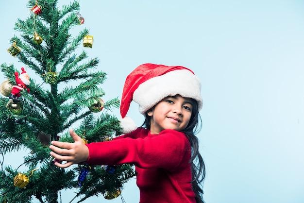 크리스마스를 축하하고 파란색 배경 위에 나무를 껴안고 귀여운 인도 아시아 소녀