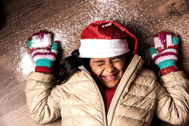 Cute little indian asian girl celebrating christmas while lying over wooden floor with snow flakes falling on her face, looking up at camera, top view