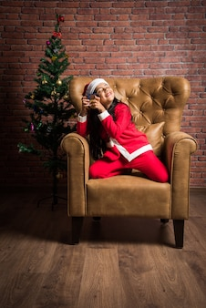 산타클로스 드레스와 모자를 쓰고 크리스마스를 축하하는 귀여운 인도 아시아 소녀, 붉은 벽돌 벽, 꿈결 같은 조명 배경에 선물과 나무가 있는 소파 위에 앉아