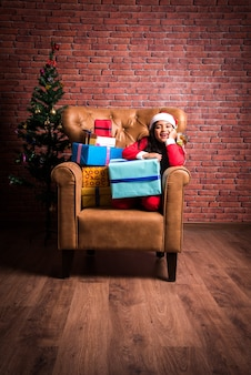 Cute little indian asian girl celebrating christmas while wearing santa clause dress and hat, sitting over sofa with gifts and tree in the background against red brick wall, dreamy lighting