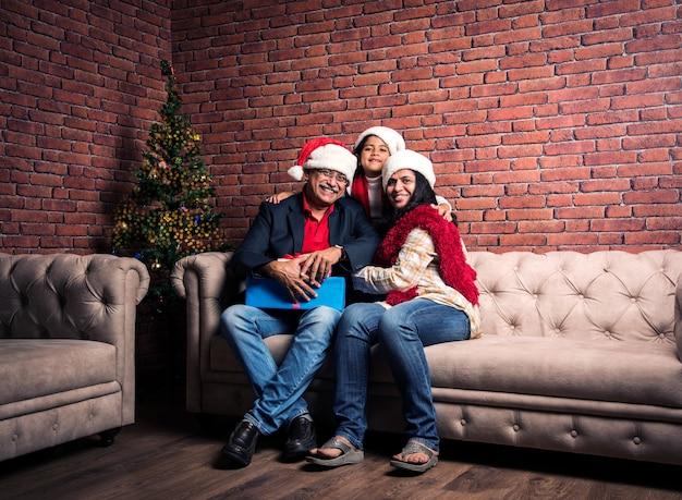 소파에 앉아 산타 모자를 쓰고 많은 선물을 들고 조부모와 크리스마스 트리와 함께 크리스마스를 축하하는 귀여운 인도 아시아 소녀