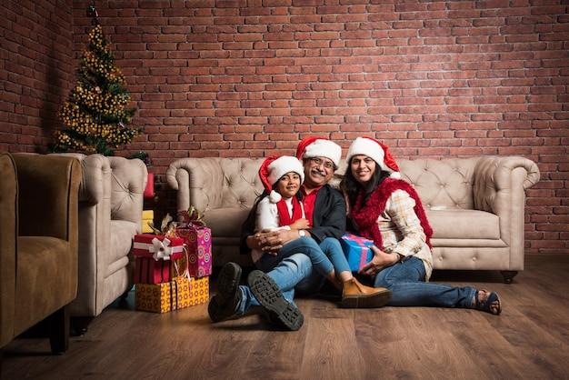 ソファの上に座って、サンタの帽子をかぶって、たくさんの贈り物をしながら、祖父母とクリスマスツリーでクリスマスを祝うかわいい小さなインドのアジアの女の子