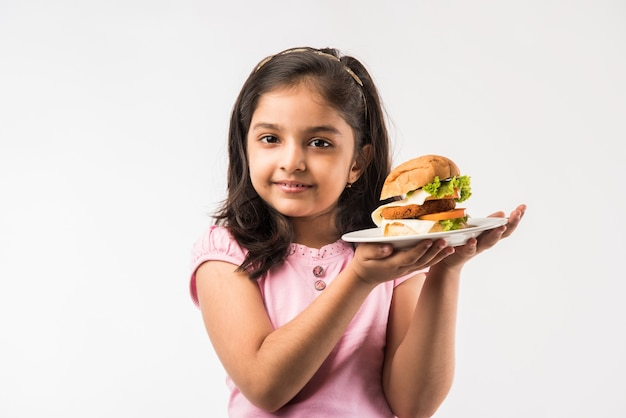 Cute little indian or asian girl eating burger on white background