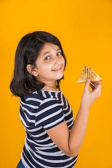 Cute little indian or asian girl eating tasty burger, sandwich or pizza in a plate or box. standing isolated over blue or yellow background.