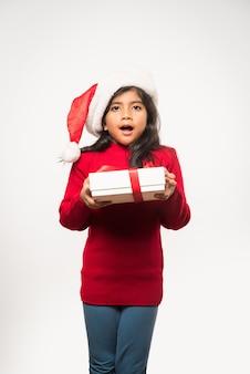 평범한 배경 위에 격리된 크리스마스 선물을 들고 있는 귀여운 인도 아시아 소녀