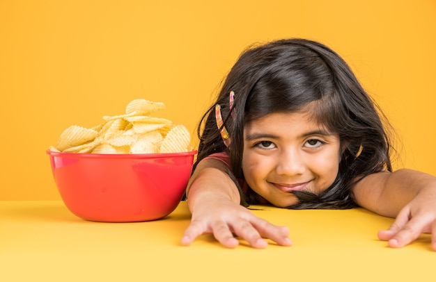 Cute little indian or asian girl kid eating chips or potato wafers in big red bowl, over yellow background