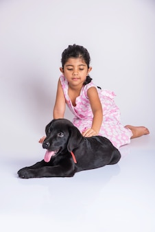 Cute little indian or asian girl playing with black labrador retriever puppy while lying or sitting isolated on white background