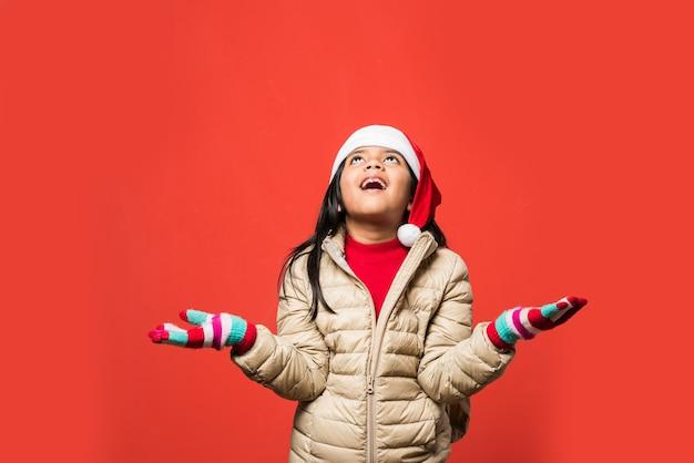산타 모자를 쓰고 귀여운 인도 아시아 소녀가 평범한 배경 위에 고립되어 서 있는 동안 크리스마스를 축하합니다