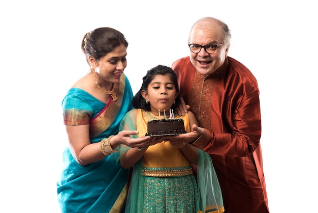 Cute little indian asian grand daughter or girl celebrating birthday with grandparents while wearing ethnic wear