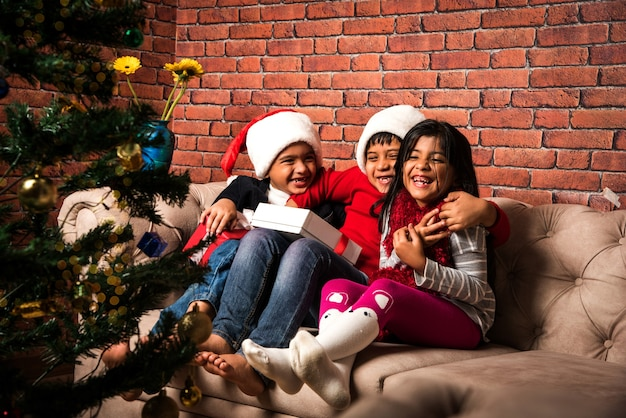 Симпатичные маленькие индийские азиатские дети празднуют рождество дома с санта-клаусом, подарками и рождественской елкой
