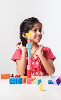 테이블에 앉아 있거나 흰색 배경 위에 절연 동안 다채로운 플라스틱 장난감 또는 블록을 가지고 노는 귀여운 작은 인도 아시아 아이