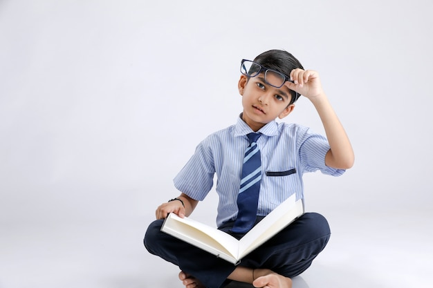 Cute little indian/asian school boy with spectacles reading book