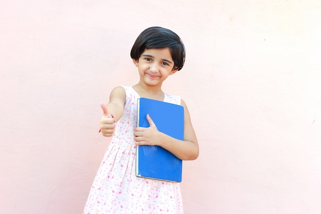Cute little indian/asian school girl showing note book