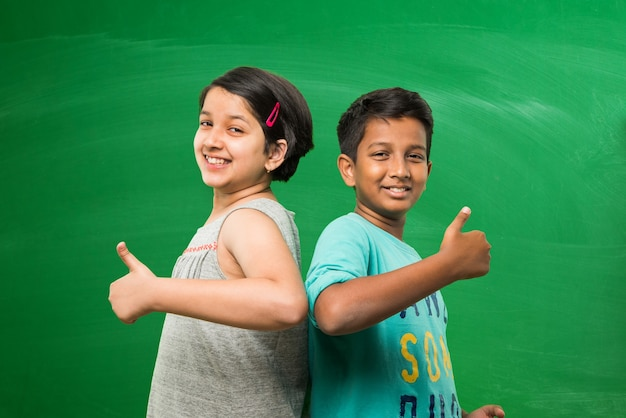 엄지손가락으로 성공 또는 승리 기호를 보여주는 빈 녹색 칠판 배경 앞에 서 있는 귀여운 인도 아시아 학교 아이들