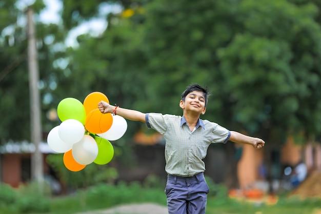 三色の風船とインドの独立記念日または共和国記念日を祝うかわいいインド少年