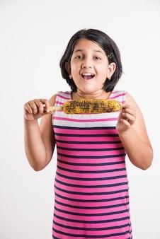 グリルコーンまたはブッタを食べるかわいいインドの少女、白い背景の上に孤立して立っています