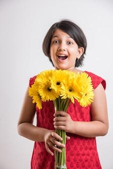 新鮮な黄色のガーベラの花の束または花束を保持しているかわいい小さなインドの女の子。白い背景の上に分離