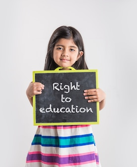 Cute little indian girl showing blank or abc written on black school slate board, isolated over white background