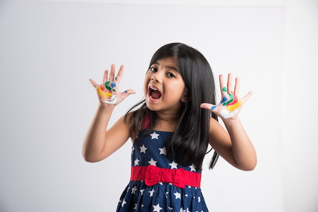 그녀의 화려한 손 또는 손바닥 인쇄 또는 그림을 보여주는 귀여운 인도 소녀 또는 흰색 배경 위에 절연 색상으로 holi 축제를 재생