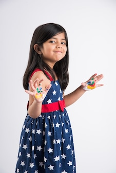 Cute little indian girl showing her colourful hands or palm printing or painting or playing holi festival with colours, isolated over white background