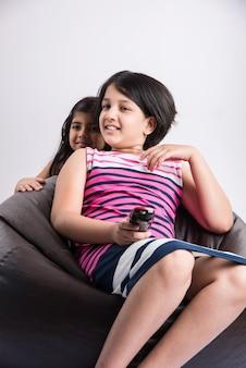 リモコンを使用してチャンネルを変更しながら、ビーンバッグの上に座って、白い背景で隔離のテレビやテレビを見ているかわいいインドの女の子