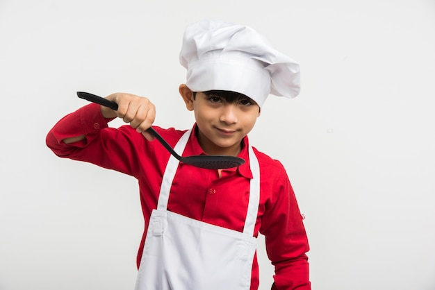 Cute little indian kid or boy dressed as a chef and holding cooking utensils, standing isolated over white background