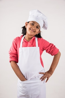 Cute little indian kid or girl dressed as a chef and holding cooking utensils or vegetables, standing isolated over white background