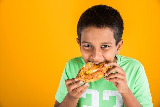 Милый маленький индийский или азиатский мальчик ест вкусный гамбургер, сэндвич или пиццу в тарелке или коробке. стоя изолированные на синем или желтом фоне.