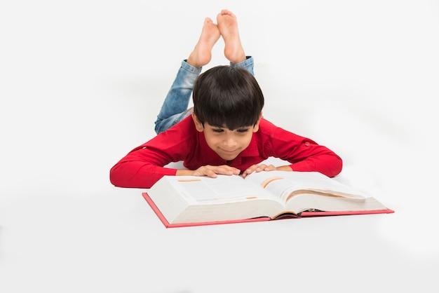 勉強のテーブルや白い床の上、白い背景で隔離の本を保持または読んでかわいい小さなインドまたはアジアの少年