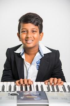 白い背景の上でピアノやキーボード、楽器を演奏するかわいい小さなインドやアジアの少年