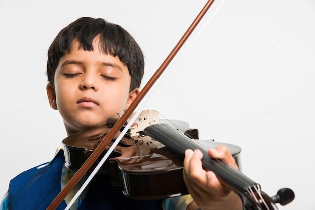 흰색 배경에 격리된 전문가처럼 바이올린을 연주하는 귀여운 인도 또는 아시아 소년