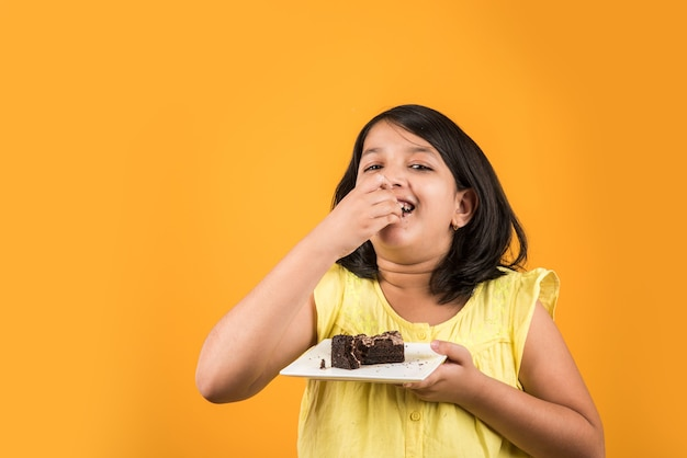 접시에 딸기 또는 초콜릿 맛 과자 또는 케이크 조각을 먹는 귀여운 작은 인도 또는 아시아 여자 아이. 화려한 배경 위에 절연
