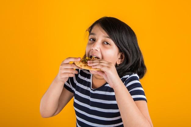 Милый маленький индийский или азиатский ребенок девочка ест вкусный гамбургер, сэндвич или пиццу в тарелке или коробке. стоя изолированные на синем или желтом фоне.