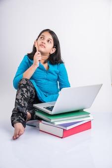 Симпатичные маленькие индийские или азиатские девочки, обучающиеся на ноутбуке или работающие над школьным проектом, лежа или сидя на полу, изолированные на белом фоне