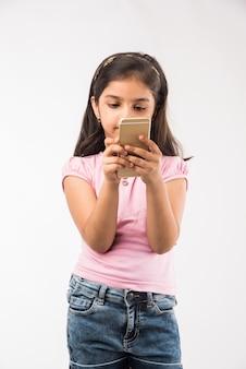 흰색으로 격리된 스마트폰을 사용하는 귀여운 인도 또는 아시아 여자 아이