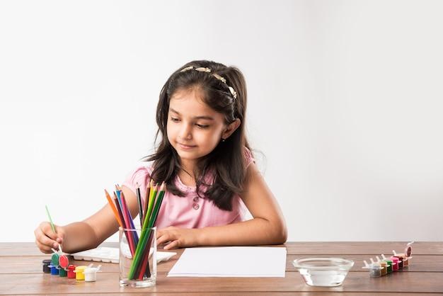 귀여운 인도 또는 아시아 소녀 색칠, 그림 또는 색상, 연필 등으로 그림