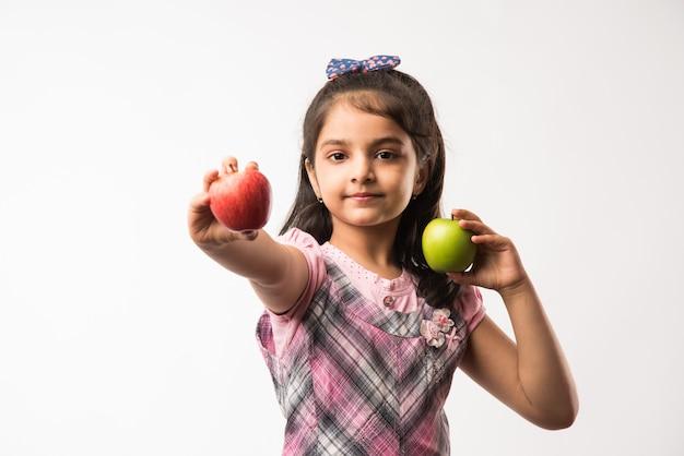 緑と赤のリンゴの果実を保持しているかわいい小さなインドまたはアジアの女の子-健康的な食事の概念