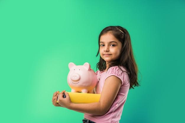 녹색 배경 위에 고립된 채 분홍색 돼지 저금통과 책을 들고 있는 귀여운 인도 또는 아시아 소녀