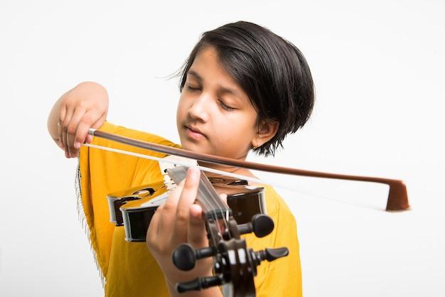 Милая маленькая индийская или азиатская девушка играет на скрипке, изолированные на белом фоне
